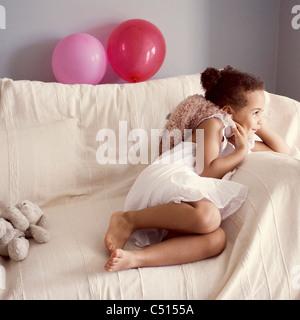 Smiling little girl lying on couch avec doudou dans la main Banque D'Images