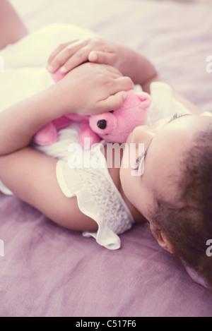 Little girl holding ours alors que la sieste Banque D'Images