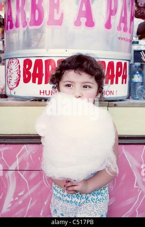 Little girl eating Cotton Candy à la juste Banque D'Images