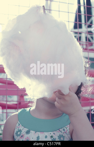 Little girl eating Cotton Candy, obscurci face Banque D'Images