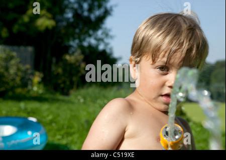 Portrait de jeune garçon jouant avec tuyau de jardin Banque D'Images