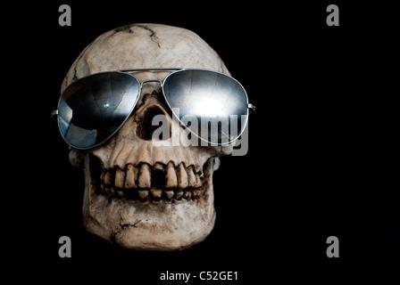 Un vieux crâne humain portant des lunettes de soleil type aviateur en miroir.