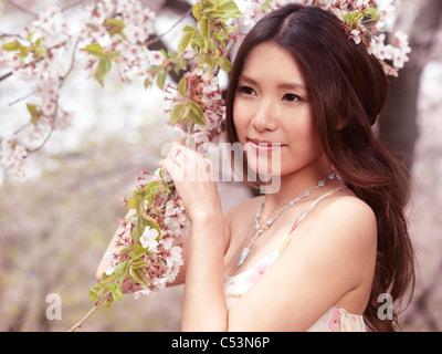 Portrait d'une belle jeune femme asiatique souriant debout à un cerisier en fleurs dans un parc Banque D'Images