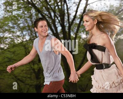 Young happy couple running ensemble se tenant la main Banque D'Images