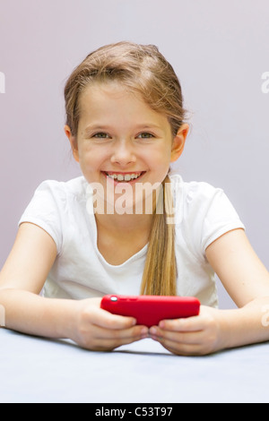 Une fillette de sept ans qui joue avec un téléphone mobile