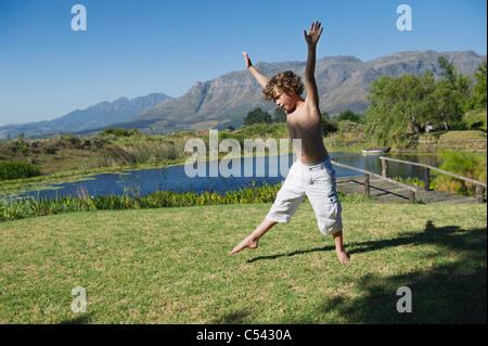 Cute little boy doing cartwheel contre mountain Banque D'Images