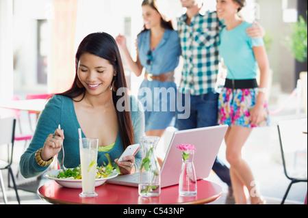 Femme mangeant de la nourriture alors que l'aide de mobile avec des gens à l'arrière-plan dans un restaurant.