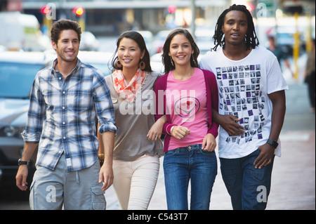Amis marchant sur la route à des voitures Banque D'Images