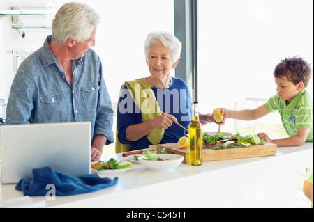 Couple avec leur petit-fils la préparation des aliments dans une cuisine Banque D'Images