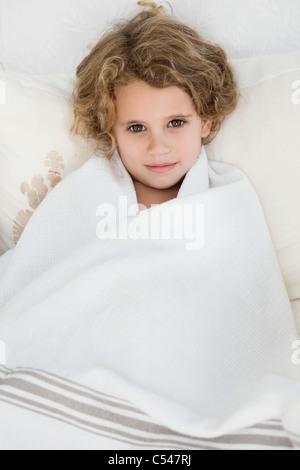 Portrait of a cute little girl enveloppée dans une serviette blanche