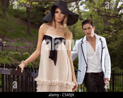 Jeune couple debout à une clôture dans un parc. Printemps scenic.