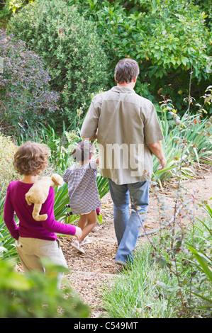 Père de deux enfants marchant dans un jardin Banque D'Images