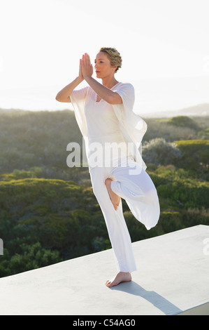 Mid adult woman practicing yoga Banque D'Images