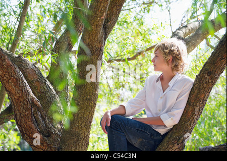 Peu contemplative boy sitting on tree branch
