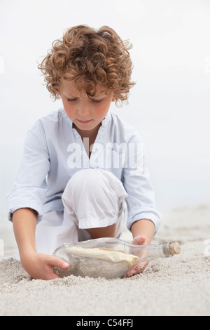 Cute boy looking at message in a bottle on beach Banque D'Images
