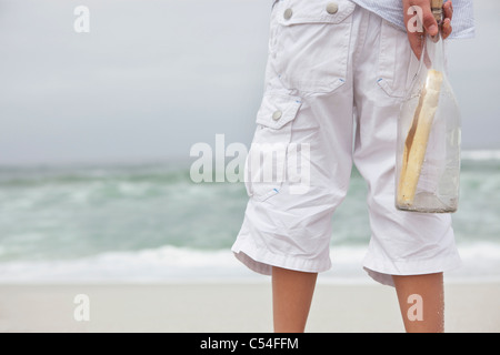 Close-up of boy holding bouteille avec message sur la plage Banque D'Images