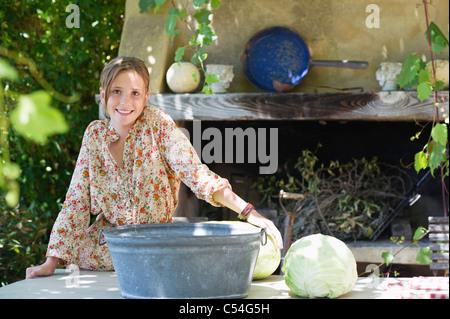 Portrait d'une petite fille avec du chou on table outdoors Banque D'Images