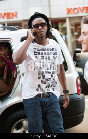 Man wearing hat et de parler sur un téléphone mobile Banque D'Images