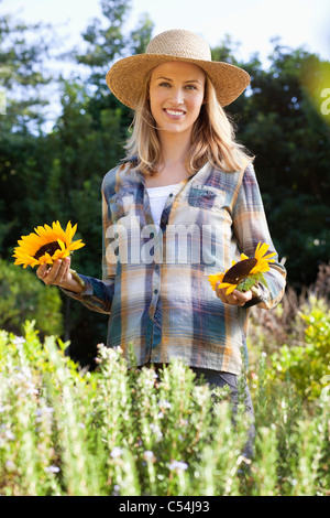 Portrait of a young woman holding tournesols dans un champ Banque D'Images