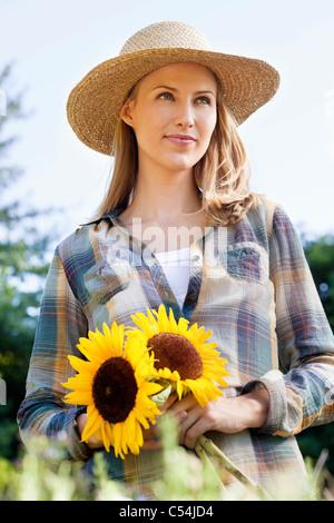 Jeune femme tenant dans un champ de tournesols Banque D'Images