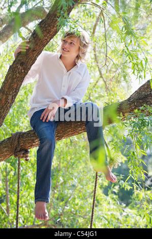 Happy little boy sitting on tree branch
