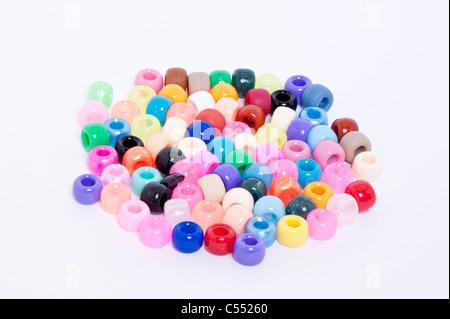 Une sélection de perles de couleur sur fond blanc Banque D'Images