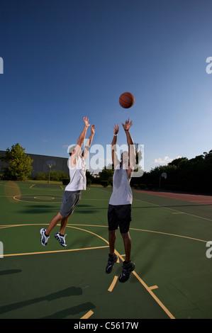 Jump shot pendant deux sur deux match de basket-ball d'être défendu Banque D'Images