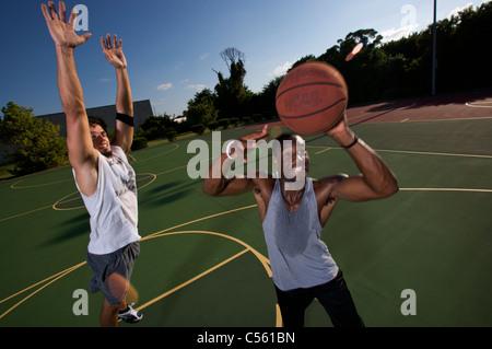 Match de basket-ball extérieur jouant les hommes