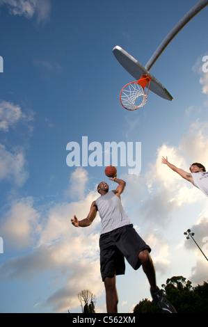 Notation mâle extérieur lors de match de basket-ball, à la recherche vers le haut vers le but Banque D'Images