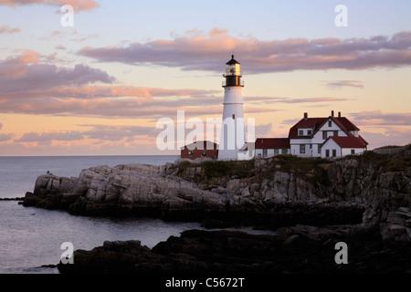 Le Portland Head Light se prépare au travail comme le soleil sur l'horizon Ouest Retraites Portland, Maine, USA Banque D'Images