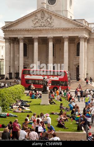 Des gens assis sur l'herbe à Trafalgar Square à l'extérieur de la Galerie nationale, St Martin dans les champs à Banque D'Images