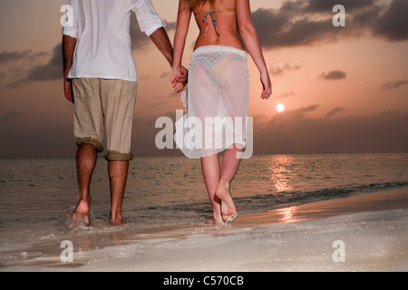 Couple en train de marcher main dans la main on beach Banque D'Images