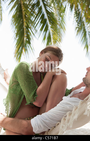 Couple sitting in hammock on beach Banque D'Images