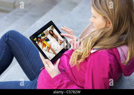 Close up of young woman reading e-magazine magazine en ligne à l'aide de Zinio application sur un iPad 2 Banque D'Images