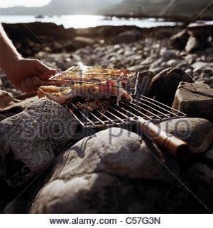 Man grilling seafood sur le feu sur la plage Banque D'Images