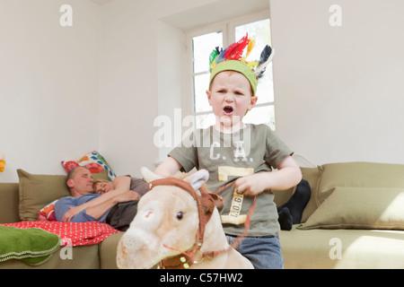 Boy in war bonnet jouant avec des jouets Banque D'Images
