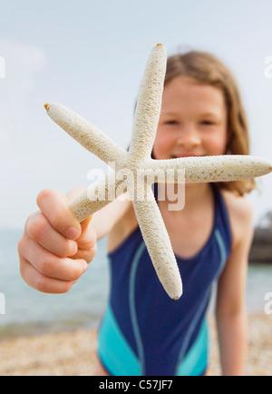 Fille de mer sur plage offrant Banque D'Images