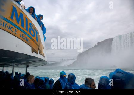 Les touristes se mouiller dans des ponchos imperméables en plastique bleu sur le Maid of the Mist à niagara falls Banque D'Images