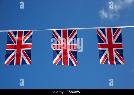 British union flag bunting bannière voler contre un ciel bleu au Royaume-Uni Banque D'Images