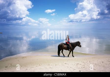 Vue latérale d'une fille à cheval sur la plage contre la mer pacifique Banque D'Images
