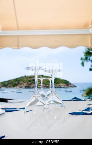 Close-up de verres de vin placé à l'envers sur la table avec la mer en arrière-plan Banque D'Images