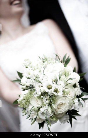 Close-up midsection of a bride holding a bouquet