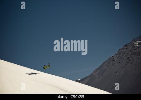 Portrait d'un skieur en action contre le ciel bleu Banque D'Images