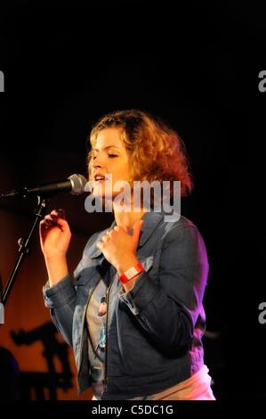 Jeune femme en chantant dans le microphone sur un fond sombre Banque D'Images