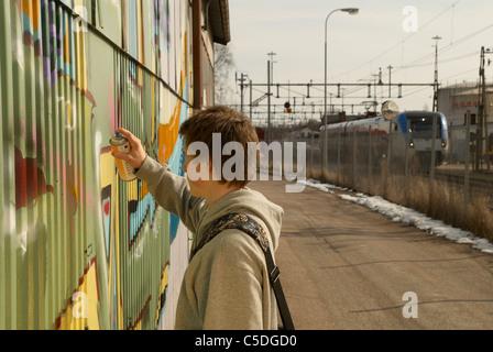 Vue latérale d'un adolescent sur le mur de graffiti de pulvérisation