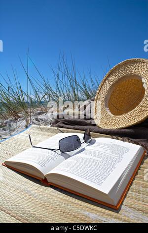 Close-up de lunettes sur livre ouvert par chapeau contre le ciel bleu clair Banque D'Images