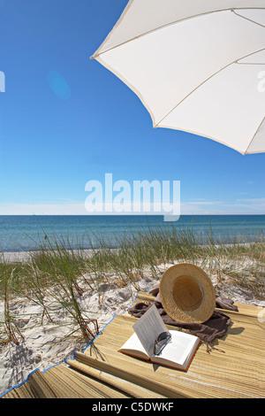 Lunettes de livre ouvert par chapeau et un parasol à plage de sable fin avec la mer en arrière-plan Banque D'Images
