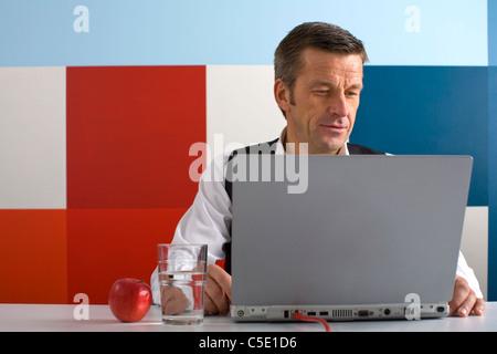 Mature businessman using laptop avec une pomme et de l'eau sur 24 contre le mur de couleur multi Banque D'Images