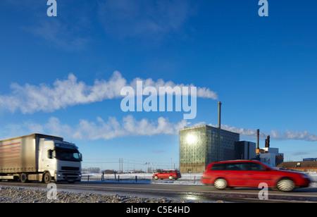 Véhicules sur rue avec dégagement de fumée de cheminée contre le ciel bleu en arrière-plan Banque D'Images