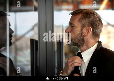 Close-up side view of a middle-aged man looking at la porte en verre et redresse sa cravate Banque D'Images